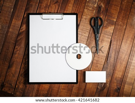 Blank stationery set. Blank paper, clipboard, business card, cd and scissors on vintage wooden table background. Blank corporate identity template. Mock-up for branding identity. Top view. - stock photo