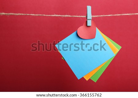 Blank sticky notes with red heart hanging against red background. - stock photo