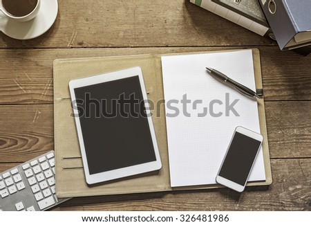 blank tablet and phone placed on an open office folder with empty white paper - stock photo