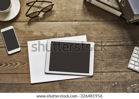 blank tablet and phone placed on an wooden desktop workspace - stock photo