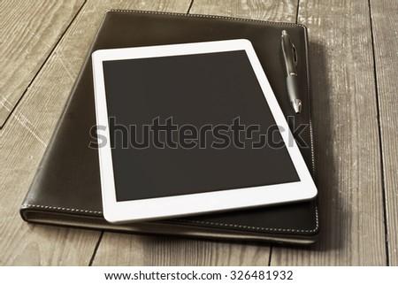 blank tablet device placed on an office folder on a wooden desktop - stock photo