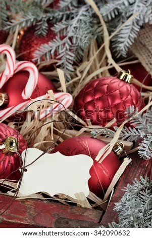 Blank tag over Christmas ornaments and candy canes packed in an old antique wooden box with snow covered pine boughs surrounding them. Extreme shallow depth of field with selective focus on tag. - stock photo