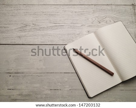 Blank textbook on white hardwood desk. Shot with smart phone. - stock photo