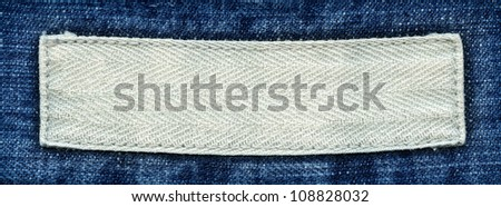 Blank textile label  sewed on a blue jeans. Can be used as background for your text. - stock photo