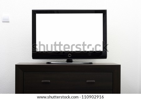 blank tv screen on brown commode against white wall - stock photo