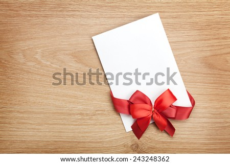 Blank valentines greeting card and red ribbon on wooden background with copy space - stock photo