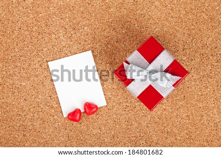 Blank valentines photo frame and small red gift box on wooden background
