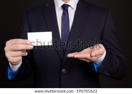 blank visiting card in young business man hand - stock photo