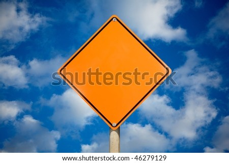 Blank warning sign against cloudy sky