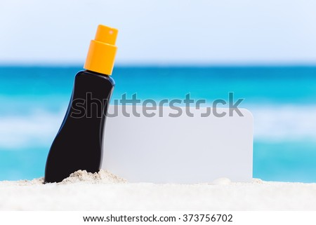 Blank white board and sunscreen protection cream on sand against turquoise caribbean sea water. Tropical summer vacation concept - stock photo