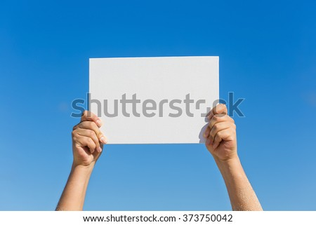 Blank white board in hands against blue sky background. Tropical summer vacation concept