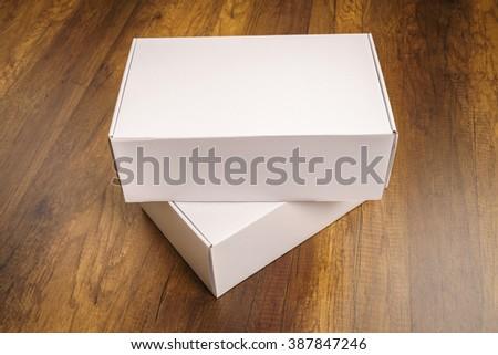 Blank white box mock up on wood background - stock photo