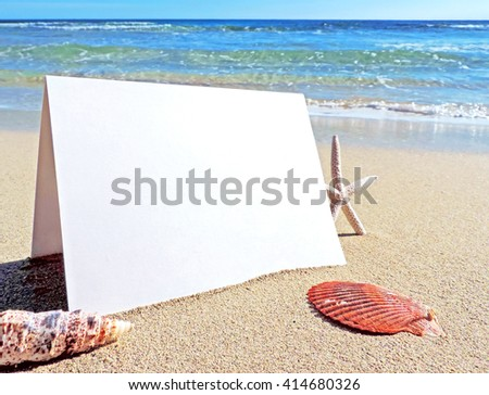 Blank white card or signboard with copy space. Beach scene with greeting card or white placard and beach decoration.           - stock photo
