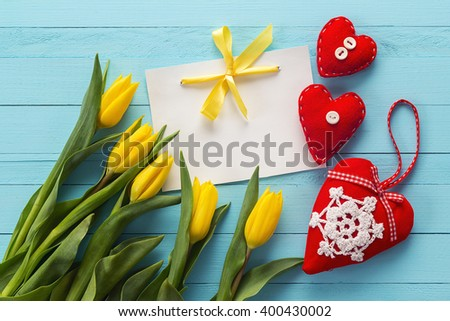 Blank white card with yellow tulips and  three red hearts on blue painted wooden planks. Place for text. Top view with copy space - stock photo