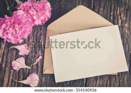 Blank white greeting card with brown envelope and pink carnation flower on wooden table with vintage and vignette tone - stock photo