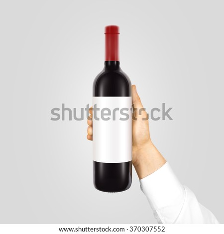 Blank white label mockup on black bottle of red wine in hand isolated. Alcohol bottle mock up presentation ready for logo design. Full drink bottle template with empty sticker. Clear tag vine bottle. - stock photo