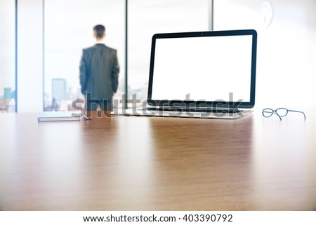 Blank white laptop on wooden desktop with city view and businessman in the background. Mock up, 3D Rendering - stock photo