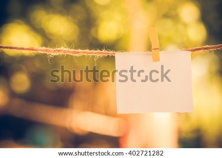 Blank white paper and clippaper  hanging on the clothesline with bokeh nature background.Designer concept.vintage or retro tone. - stock photo