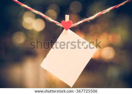 Blank white paper and red clip paper heart hanging on the clothesline with bokeh nature background.Designer concept.vintage or retro tone. - stock photo