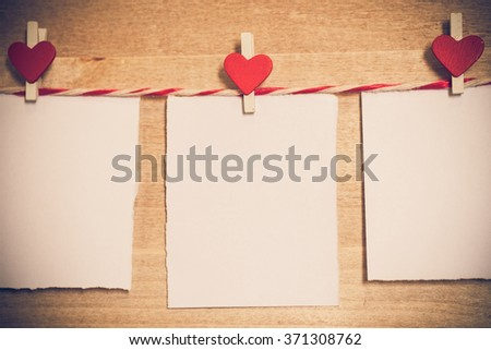 Blank white paper and red clip paper heart hanging on the clothesline with wood background.Designer concept.vintage or retro tone. - stock photo