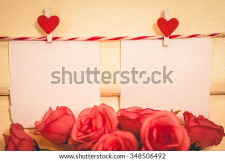 Blank white paper and red clip paper heart hanging on the clothesline with wooden and pink rose background.Designer concept.Vintage or retro tone. - stock photo