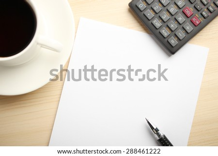 Blank white paper is on the table with calculator and coffee aside. - stock photo