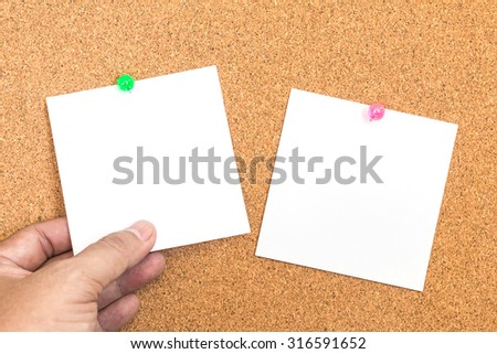 Blank white paper note with green pin on corkboard  with hand holding - stock photo