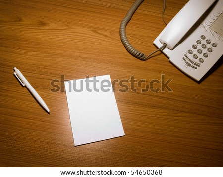 Blank white paper on the wooden working desk with the pen and telephone,shot taken from above - stock photo
