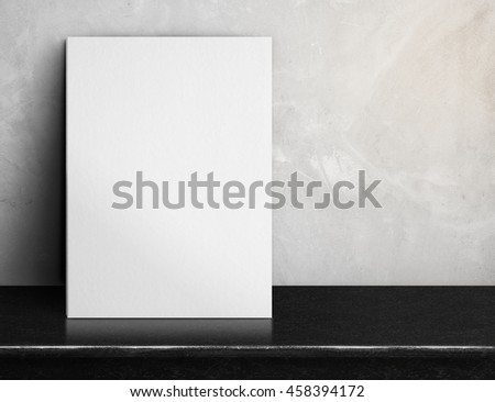 Blank White paper poster on black marble table at grey concrete wall,Template mock up for adding your design and leave space beside frame for adding more text