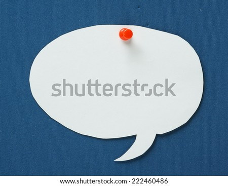 Blank white paper speech or talking bubble pinned to a blue notice board with a red push pin - stock photo