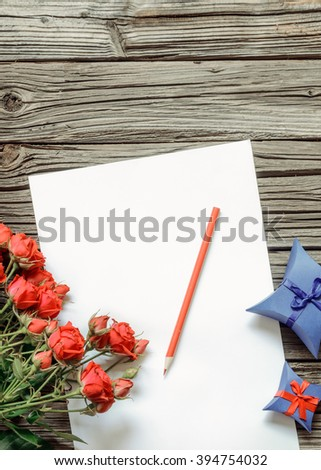 Blank white paper with copy space on top of weathered wooden surface surrounded by bundle of roses, pair of gift boxes and pencil - stock photo