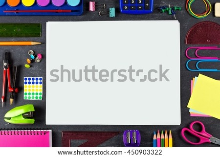 Blank white paper with frame of school supplies over a chalkboard background - stock photo