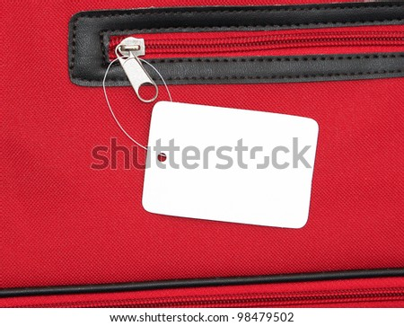 Blank white price tag on red zippered bag for your text - stock photo