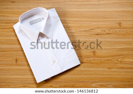 blank white shirt folded on a wooden background, with text space.  - stock photo
