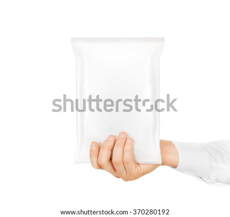 Blank white snack bag mock up hold in hand isolated. Clear white chips pack mockup. Cookie, candy, sugar, cracker, nuts, jujube supermarket foil plastic package ready for logo design presentation. - stock photo