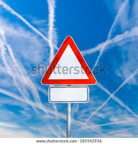 Blank white triangular traffic warning sign on a signpost against a sunny blue sky with crisis-crossing contrails from jetliners with copyspace for your text.