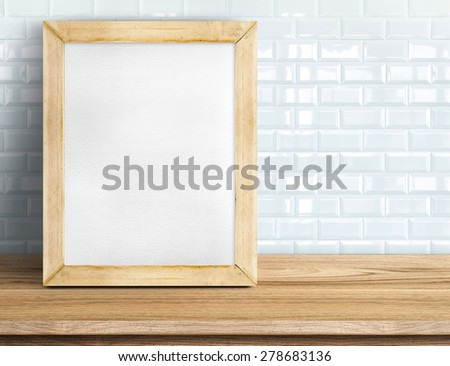 Blank whiteboard wood frame on wooden table at white tile wall,Template mock up for adding your design and leave space beside frame for adding more text. - stock photo