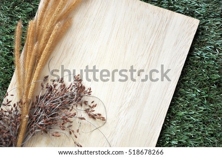 Blank wooden board with dried flowers put on green grass