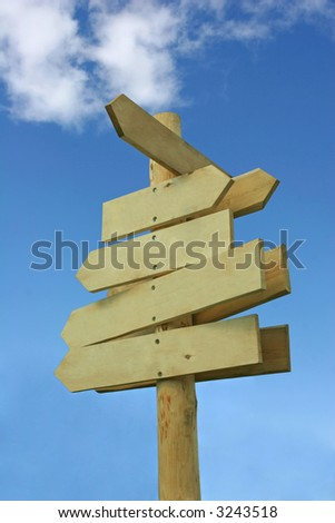 Blank wooden direction signpost against a blue sky - stock photo