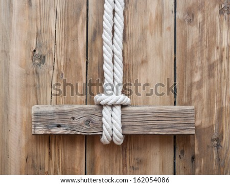 blank wooden signboard on aged wooden wall  - stock photo