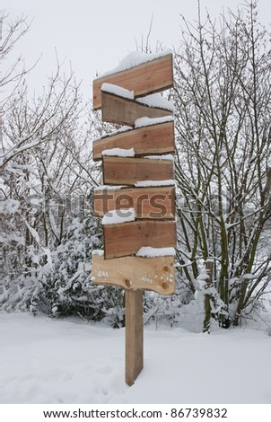 Blank wooden signpost covered in snow on a winter day. - stock photo