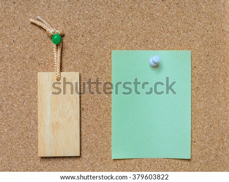 Blank wooden tag and green paper on cork board with tack pin for text and background - stock photo