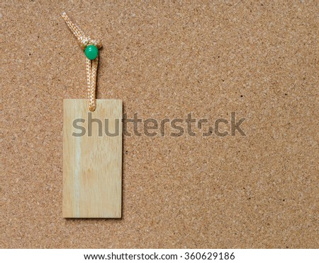 Blank wooden tag hang on cork board with green tack pin for text and background - stock photo