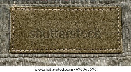 blank yellow-brown  leather label on textile background