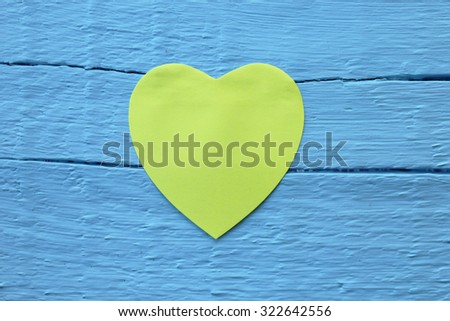 Blank yellow paper note with heart shape on grunge blue wooden background with copy space - stock photo