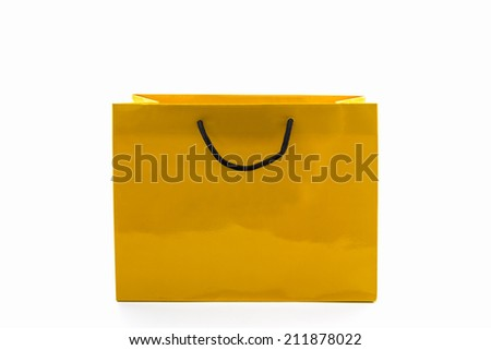 Blank yellow paper shopping bag on white background. - stock photo