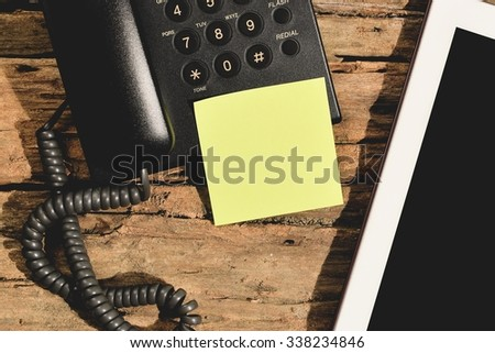 blank yellow paper stick on black telephone  - stock photo