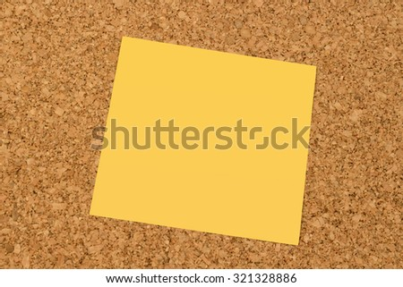 Blank yellow sticky note on an office cork board
