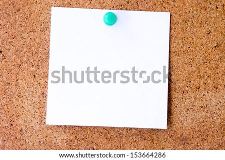 Blank yellow sticky note pined on a cork bulletin board. - stock photo