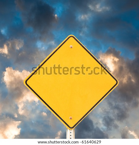 Blank yellow warning road sign with dramatic sky background ready to carry your message. - stock photo